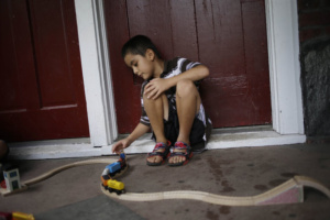 In this July 17, 2014 photo, Kevin Torres, 7, plays on the front porch of his apartment building in Huntington Station, N.Y. Since arriving from El Salvador in May 2014, Torres lives with his mother in a two-story colonial divided into four different units. The house is rented by different immigrant families from different Central American countries. (AP Photo/Seth Wenig)