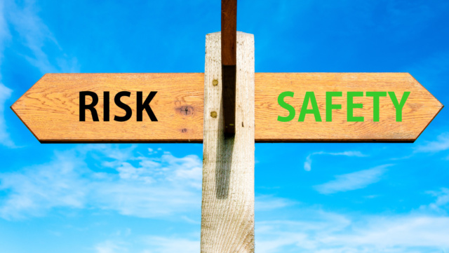 Wooden signpost with two opposite arrows over clear blue sky, Risk versus Safety messages, Right choice conceptual image